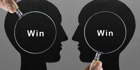 Two magnifying glasses held over two silhouettes of heads with the word 'win' in each